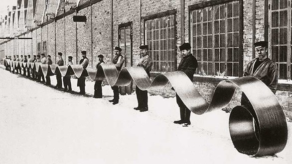 Historical photo of persons outside a factory.