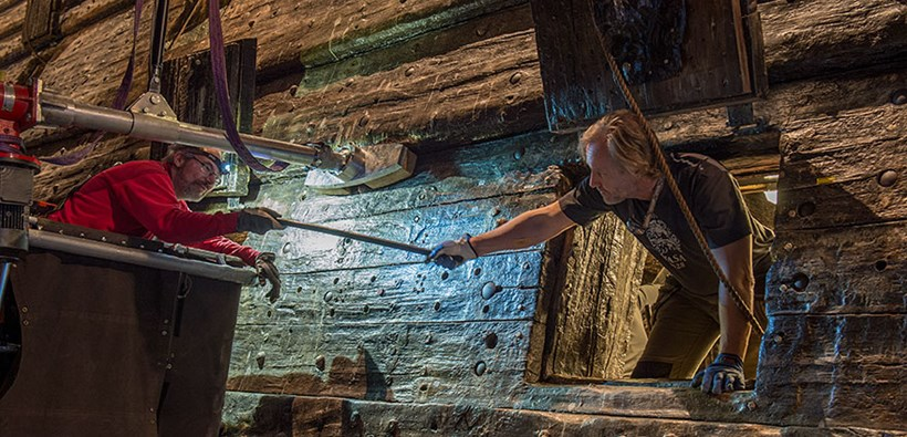 Two persons exchanging a bolt at the Vasa ship.