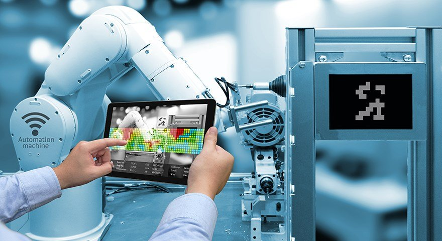 Hands holding a tablet in front of an industrial robot.